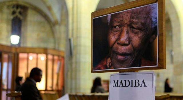 Un hombre sentado durante una oración por Mandela. | Afp