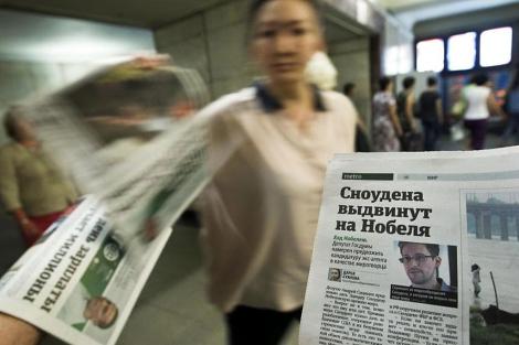 Una empleada distribuye periódicos donde aparece la imagen de Snowden, en Moscú. | Reuters