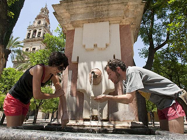 Dos turistas se refrescan en una fuente de Córdoba. | Madero Cubero