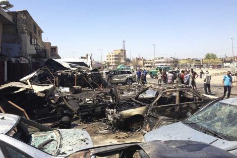 Residentes junto a uno de los coches bomba en el distrito de Hurriya, Bagdad | Reuters