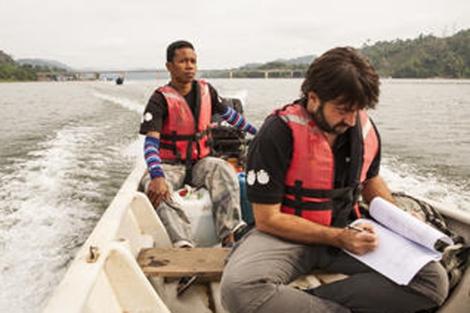 Uno de los científicos revisando un manuscrito en una lancha en Guatemala. |UNMC