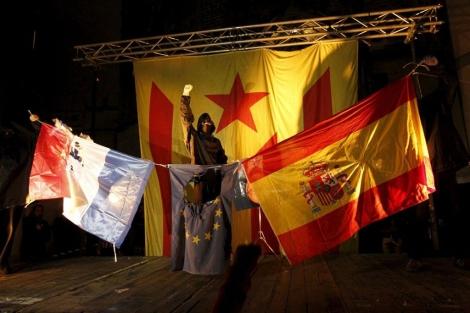 Uno de los encapuchados celebra la quema de los símbolos. | Jordi Soteras