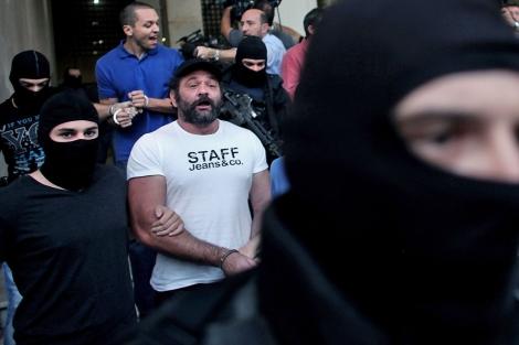 Imagen de dos de los diputados de Amanecer Dorado imputados, escoltados por la policía hasta el tribunal