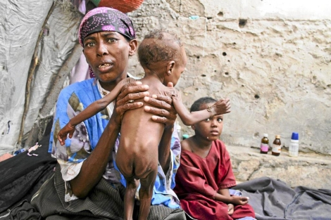 Una mujer sostiene a su hijo de dos años en un centro de distribución de urgencia somalí | Efe