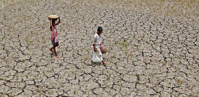 Un campesino indio y su hijo en Agartala, durante la sequía de 2009.| AFP