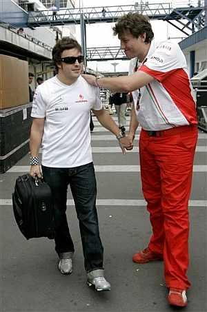 Alonso recibe el apoyo de un mecánico de Ferrari al abandonar el circuito de Interlagos. (Foto: AP)