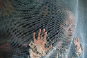 Siama Marja, de tres años, juega protegida por una tela antimosquitos en Kenia (Foto: EFE | Stephen Morrison)