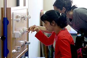 Una trabajadora de la Fundación Numen ayuda a una niña con parálisis. (Foto: José Aymá)