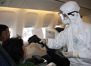 Sanitarios protegidos examinan a pasajeros procedentes de México en el aeropuerto de Shangai (Foto: Getty Images | Zhao Yun)