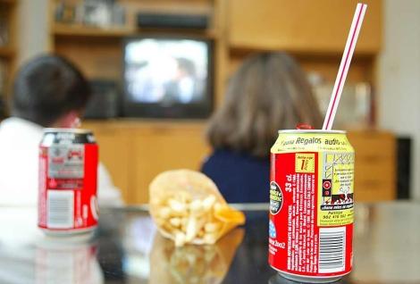 Dos niños toman refrescos y patatas fritas. | Foto: Bernabé Cordón