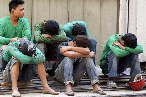 Varios trabajadores echan una cabezada en la pausa de medio día. | Reuters | Erik de Castro