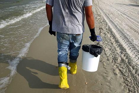 Un hombre recoge fuel en las costas de Alabama. | Win McNamee