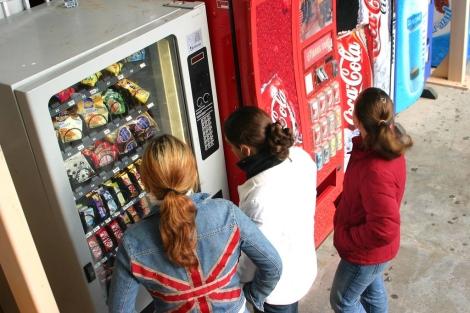 Niñas sacando alimentos y bebidas de máquinas expendedoras. | Enrique Calvo