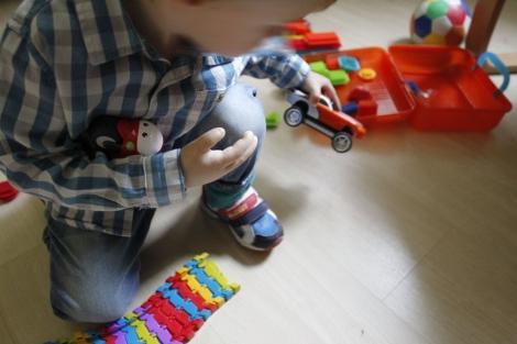 Pablo, que tiene una protesis de mano, juega con un coche. | Sergio González
