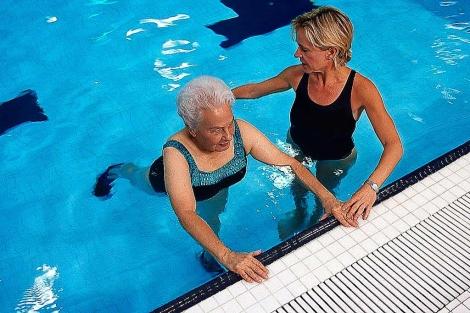 Una mujer realiza ejercicios en una piscina.| El Mundo