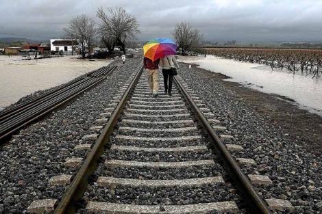 Una pareja pasea por las vías del tren. | EL MUNDO