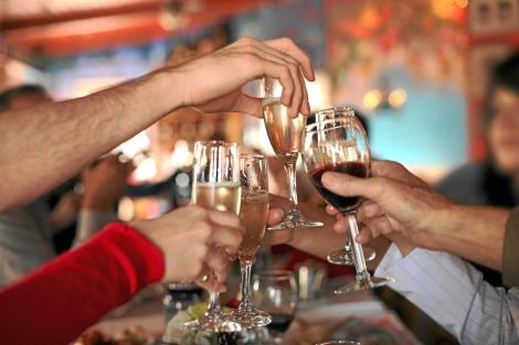 Varias personas brindan con copas de vino y champán. | Shutterstock