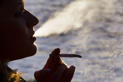 Una mujer fumando en el parque de El Retiro de Madrid. | El Mundo