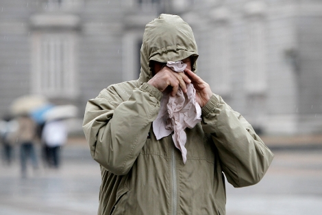 Un hombre se suena la nariz bajo la lluvia.| Alberto di Lolli