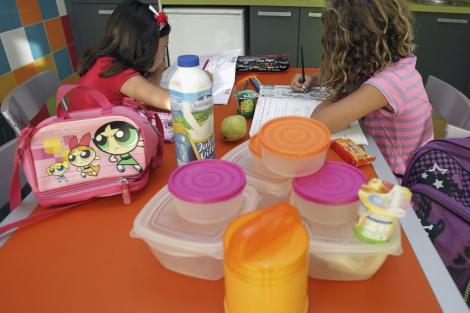 Unas niñas en una mesa con varios tuppers