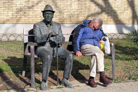 Un hombre duerme sentado en el banco de un parque