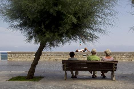 Ancianos sentados en un banco junto al Kursaal, en San Sebastián.