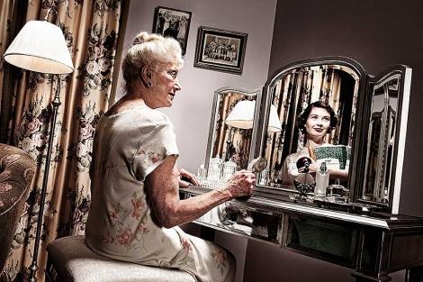 Una anciana se refleja en un espejo, donde puede verse una reproducción de cómo sería ella de joven