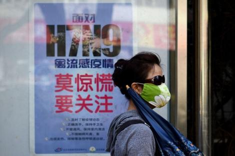 Una mujer pasea delante de un cartel que explica cómo evitar la infección por H7N9. | Afp