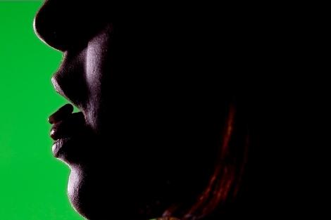 Una mujer sostiene una pastilla en la punta de la lengua