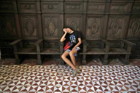 Un turista duerme a las puertas del Museo Arqueológico de Sevilla. | Marcelo del Río
