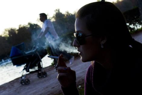Una mujer fumando en el parque del Retiro, Madrid. | Gonzalo Arroyo