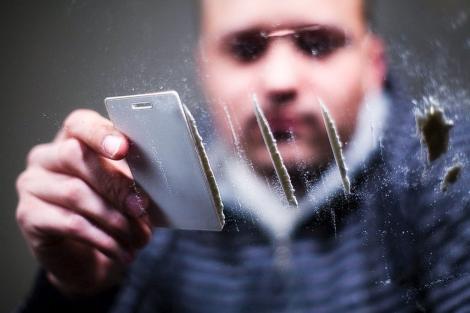 Un joven prepara varias rayas de cocaína. | SHUTTERSTOCK