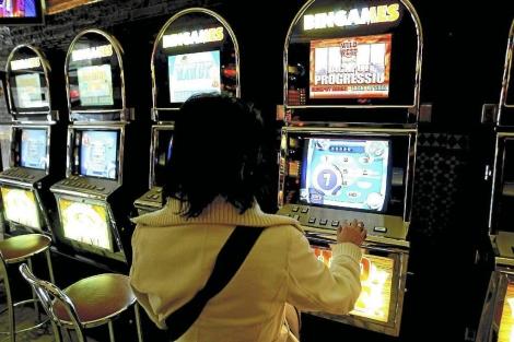 Una mujer jugando a una máquina tragaperras. | Antonio Moreno