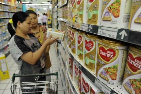 Una mujer mira una de las latas de leche Dumex en un supermercado de china. | Reuters