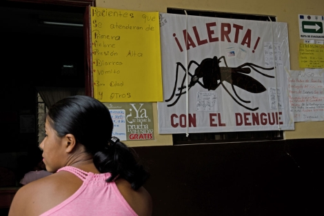 Una mujer frente a un cartel con instrucciones sobre el dengue. | MSF