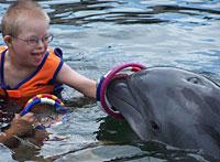 Michael, un niño con síndrome de Down, realizando una de las actividades terapéuticas con un delfín. | ISLAND DOLPHIN CARE