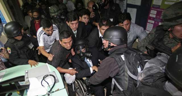 Correa, con máscara de gas y en silla de ruedas, abandona el hospital escoltado. | Ap