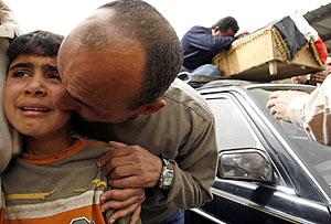 Un hombre consuela a su hijo durante un entierro. (Foto: REUTERS)