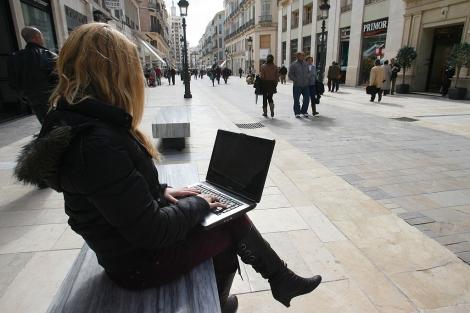 Mujer navega por internet con su portátil.